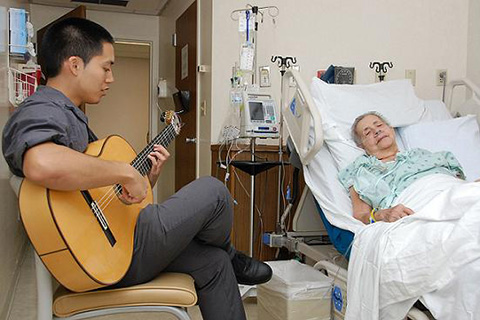 Student plays the guitar for a patient